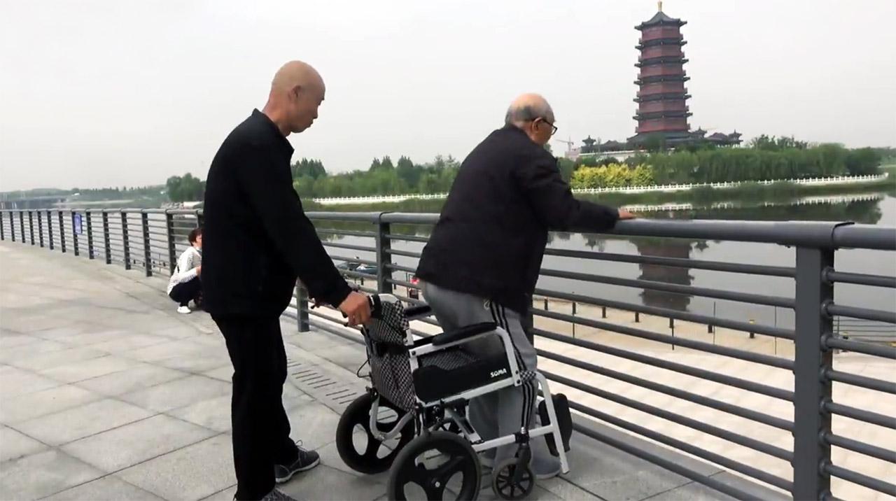 暖心!62岁大叔轮椅推86岁父亲遛弯 推着一种幸福