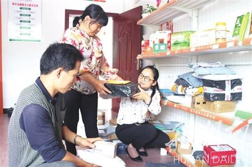 益阳市依托村民服务中心建设多功能商务中心。图为桃江县修山镇花桥港村商务代办员为村民分拣包裹。