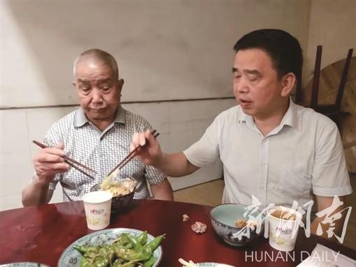 肖飞在敬老院陪父亲一起吃饭。 黄田 摄