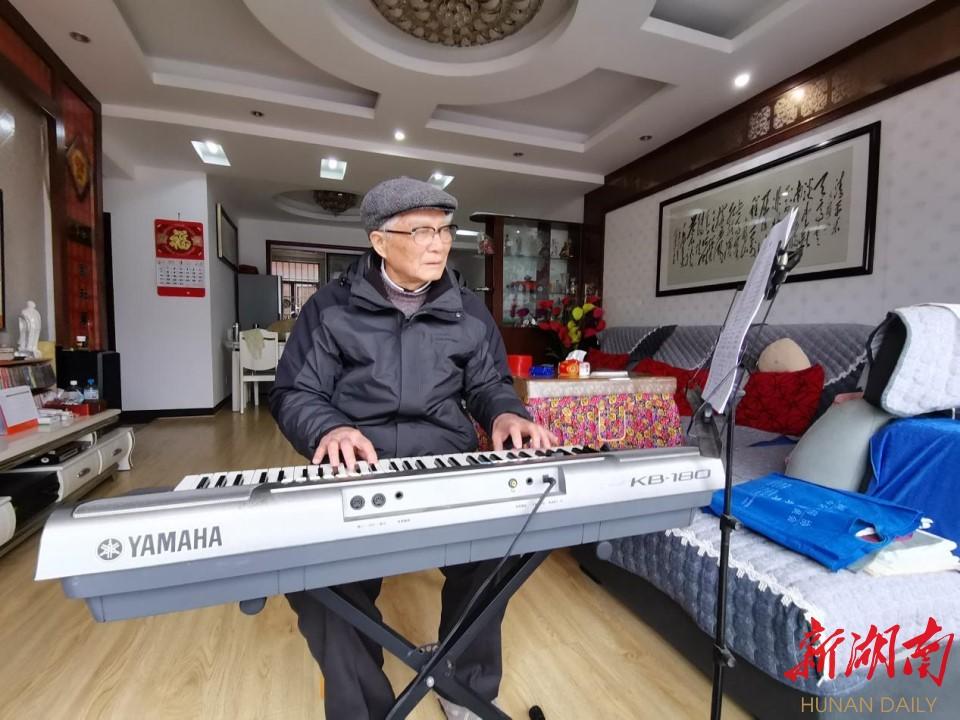 图为陈义庭老人在弹奏歌曲。