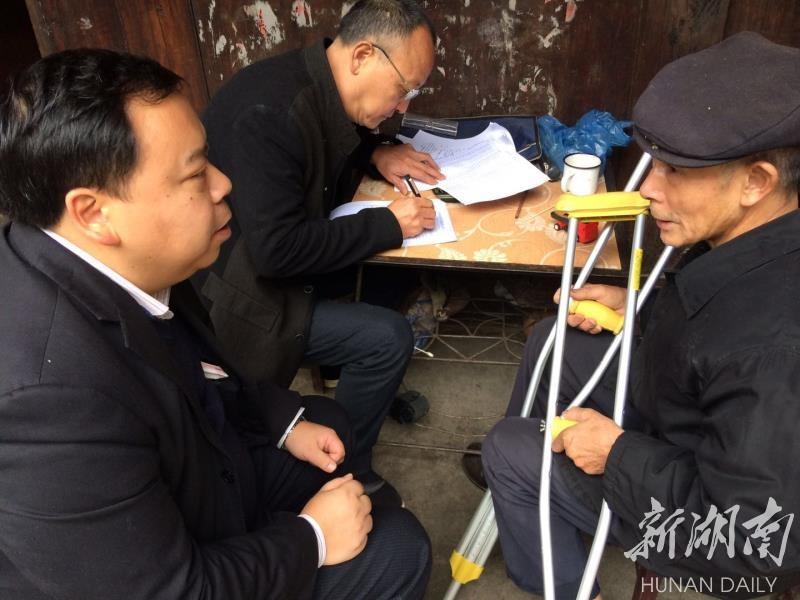 湖南坡茶业负责人龙文初带着员工走访贫困户,建立贫困户档案。