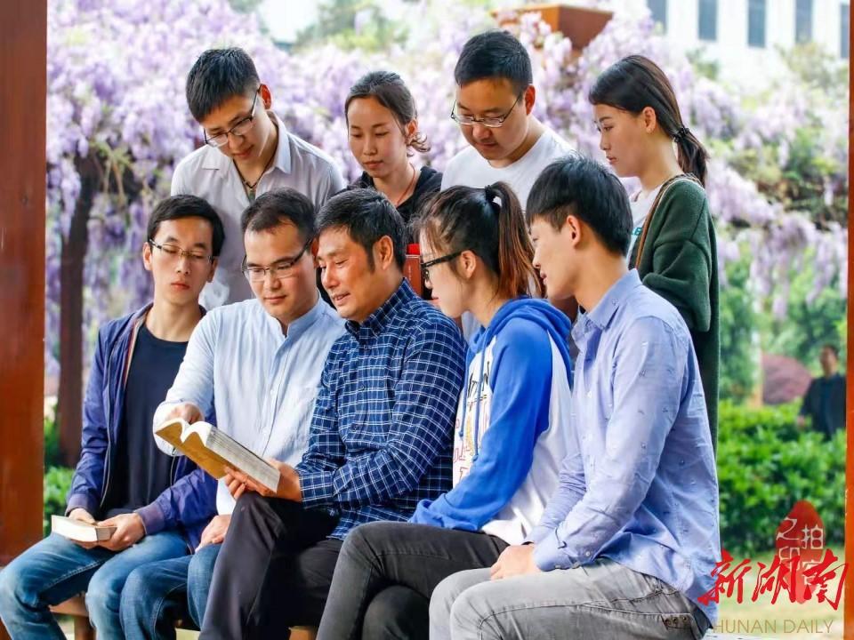 图为王诚喜和他的学生们在一起研究课题。