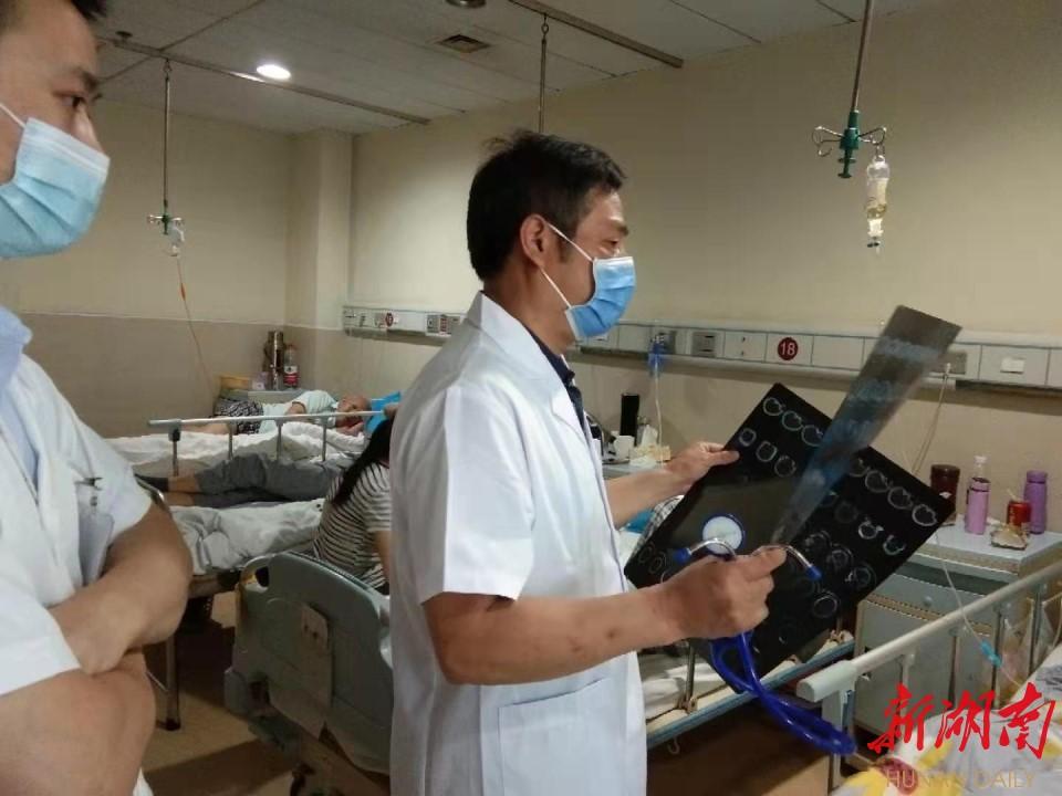 图为王诚喜在病房查房。