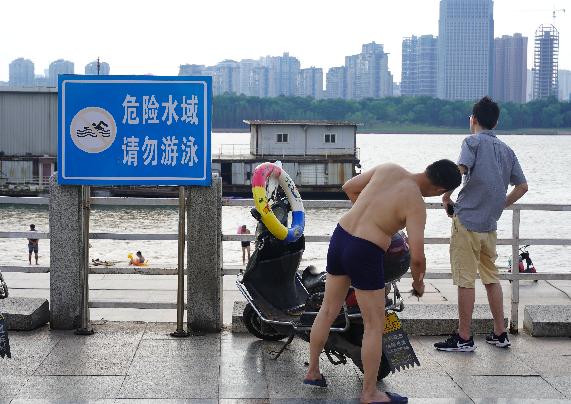 无视警示牌,不少市民带着孩子在危险水域野泳消暑