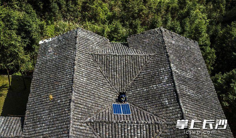 """为照顾老人生活,张坊镇及上洪村多次帮张福继安装水力发电机,但维修不易。于是,村上和爱心人士发起了一场""""用爱发电""""的众筹行动——为老人装一个太阳能发电机。4月19日,易承业爬上了老房子的屋顶给张福继装好了太阳能板。"""
