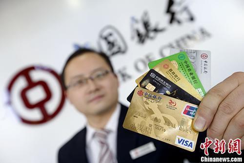 资料图:山西太原的银行工作人员展示各类信用卡。 <a target='_blank' href='http://www.chinanews.com/'>中新社</a>记者 张云 摄